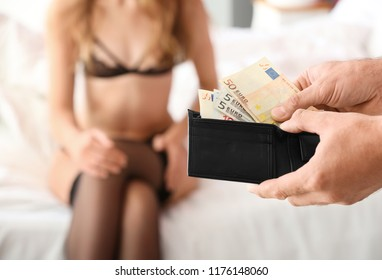 Client paying prostitute for her work in brothel