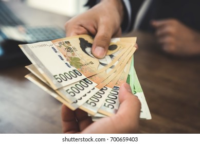 Client receiving money, South Korean Won currency,  from a businessman - buying, payment and bribery concept