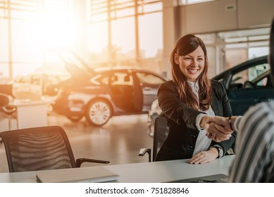Client shaking hands with car dealer in showroom.