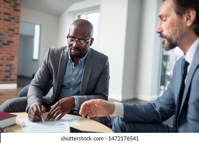 Client signing agreement. Bearded qualified and experienced tax lawyer speaking with client signing agreement