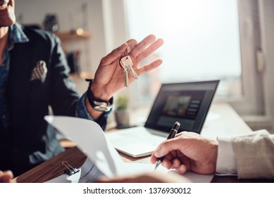 Client signing rental agreement contract while real estate agent sitting across the desk and holding keys