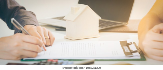 Client signs document regarding real estate activity next to lawyer or real estate agent sitting at office desk. Business concept of selling and buying real estate.