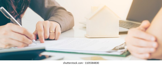 Client signs document regarding real estate activity next to lawyer or real estate agent sitting at office desk. Business concept of selling and buying house.