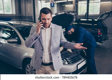 Client talking on the smartphone, he is  displeased, complaining about bad service, arguing on phone, having conflict during telephone conversation  while repairman fixing his car in workshop