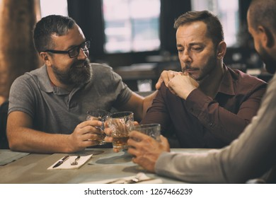 Clients of bar sitting and communicating. Male friends spending time together, drinking alcoholic beverages and talking. Man in spectacles smiling. Concept of friendship.