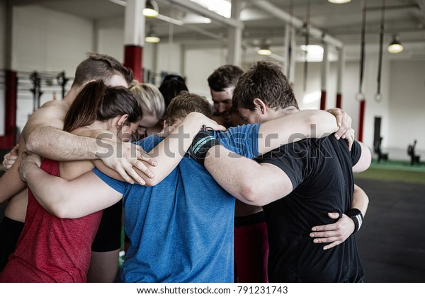 Clients Standing In Huddle At Gym