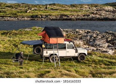 Clifden, Ireland- July 25, 2020; A man camping on the west coast of Ireland in a Land Rover with a roof tent