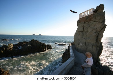 A cliff diver plunges into the pacific ocean.