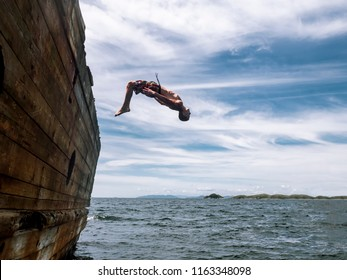 Cliff jumping: A young guy in shorts jumps into seawater from the side of an old ship.