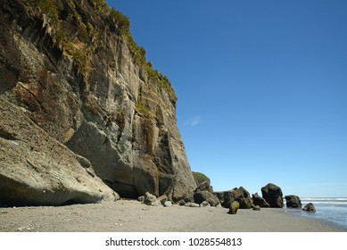 a cliff at low tide on a West Coast beach, South Island, New Zealand