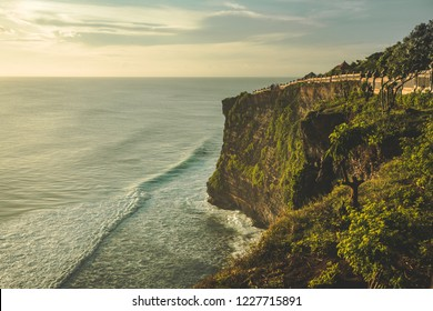 Cliff, ocean shore, tourist path. Panorama. Uluwatu. Bali island. Indonesia. Stunning scenery the high green-capped rock over the Indian ocean. Shot taken from the Pura Luhur Uluwatu Temple.