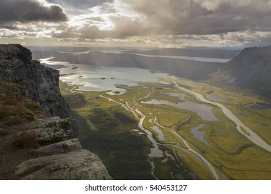 Cliff overlooking big river delta in lake autumn landscape with rain from clouds