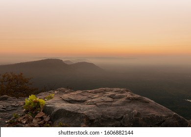 Cliff stone located part of the mountain rock on the top hill with mountain view at sun rise time.