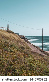 Cliff top coastal walkway and posts with view of the Atlantic ocean on a sunny summer day. Taken in Praia das Maçãs, Portugal.