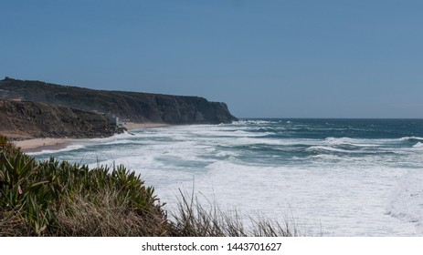 Cliff top view of Praia Grande from Praia das Maçãs, Portugal & the waves of the Atlantic ocean. Taken on a sunny summer day.