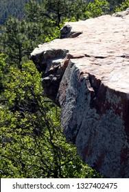 Cliff top view of a rocky overhang above the tree tops; Mogollon Rim in Apache-Sitgreaves National Forest in Arizona