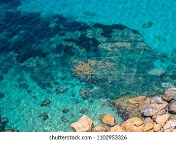 Cliff and turquoise sea of the Mediterranean, in the area of Cala D'hort, in front of Es Vedrá, in Ibiza, Spain