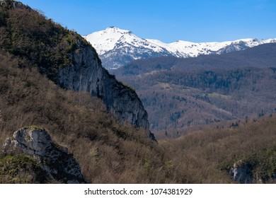 Cliffs, forest and snow-capped mountains in Ariege in the french Pyrenees