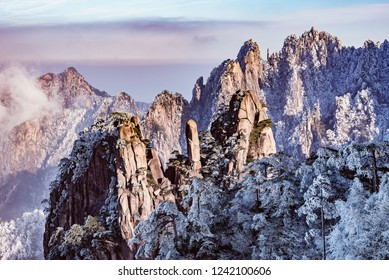Cliffs in Huangshan National park at foggy winter evening. China.