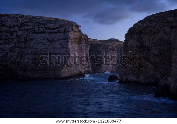 Cliffs in Island of Gozo (Dwejra Bay) at dusk. On right side Fungus Rock. Winter, Malta.
