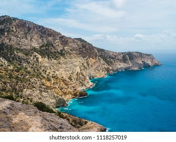 Cliffs, mediterranean turquoise sea and mountains, of the natural park of Cala D'hort, in Ibiza, Spain. It is a trekking route that leads to the tower des savinar to be able to contemplate Es Vedrá.