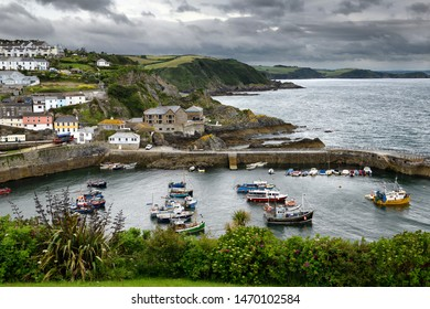 Cliffs at Mevagissey Bay on the Atlantic Ocean and fishing boats in the harbour of Mevagissey village with clouds Cornwall, England - June 11, 2019