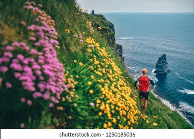 The Cliffs of Moher in Ireland. Young tourist looking at the blue sea. Colorful flowers on the meadow.
