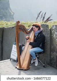 CLIFFS OF MOHER, IRELAND-September 18, 2014: Tina a harp player entertaing tourists at Cliffs of Moher, Ireland.
