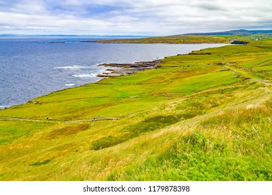 Cliffs of Moher trail with Doolin village and farm fields in background, Clare, Ireland
