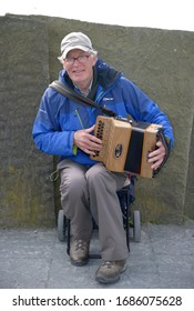 CLIFFS OF MOHR, IRELAND-September 18, 2014: Alan, playing accordion at Cliffs of Moher in Ireland.