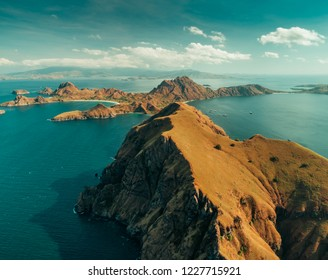 Cliffs, mountains, ocean. Aerial drone shot. Komodo. Stunning overview the huge limestone cliffs surrounded by the calm ocean. Komodo National Park, Indonesia. UNESCO World Heritage Site.