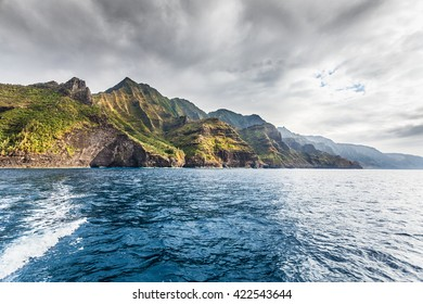 Cliffs of the Na Pali coast in late afternoon sun with darkening skies above. Kauai, Hawaii