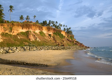 Cliffs on the beach near the ocean over blue sky
