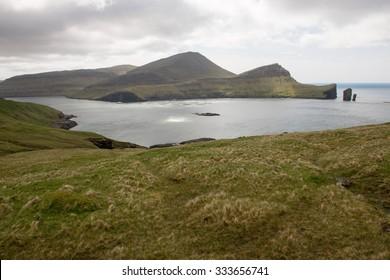 Cliffs on Vagar Island on the Faroe Islands with salmon farm