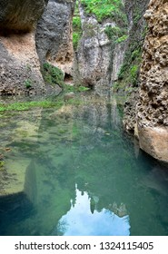Cliffs reflected in the water at the bottom of the El Tajo gorge in Ronda