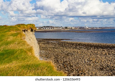Cliffs, rocks and ocean in Silverstrand Beach with Salthill building in background, Galway, Ireland