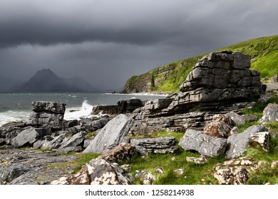 Cliffs and shore north of Elgol Port na Cullaidh with Red Cuillin Mountains under dark clouds on Loch Scavaig Isle of Skye Scotland UK