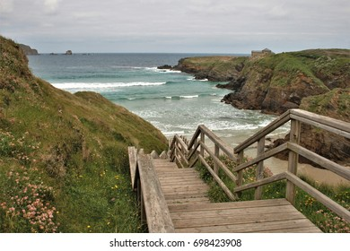 Cliffs and wooden staircase with handrails to go down to the beach of Covas, A Coruna, Galicia, Spain,