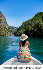 cliffy rocks of Verdon Gorge at lake of Sainte Croix, Provence, France, Provence Alpes Cote d Azur, blue green lake with boats in France Provence. Europe, young woman in peddle boat looking at river