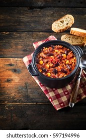 Clili con carne stew in black iron pan served with bread over napkin on rustic wooden table with vertical copy space