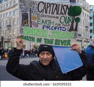 Climate change and anti-capitalism protest at Oxford Circus, man holding sign. London - 18th January 2020