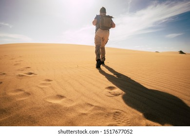 Climate change concept with man walkling with backpack in. arid sand desert under the warm sun and no water - danger for the future of the planet - wild nature concept