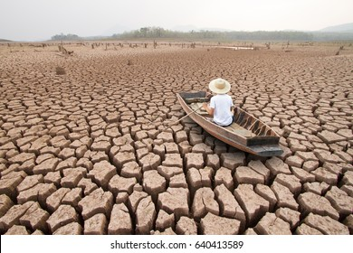 Climate change, The man on wood boat at large drought land - Shutterstock ID 640413589