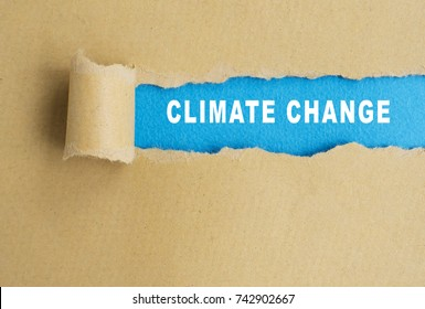 Climate change words on torn paper background.