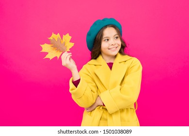 Climate changes. Autumn is here. Small girl fall outfit red background. Hello october. Little girl welcome autumn. Kid girl cute face hold maple leaf. Enjoy season. Child with autumn yellow leaf.