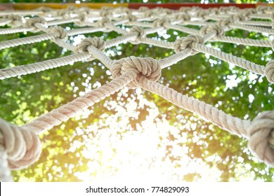 climb net rope close up background and textures,Rope Netting as Healthy Exercise,rope net for adventure game in day light,Acargo net stretched out between trees as part of an adventure climbing course