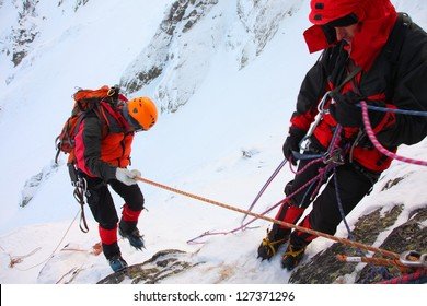 Climber abseiling from the mountain in winter