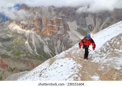 "Climber ascending the final stepd of via ferrata ""Lipella"" on Tofana massif, Dolomite Alps, Italy"