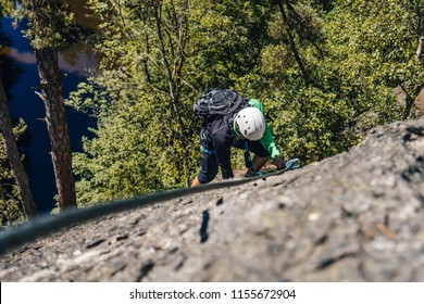 A climber ascending via ferrata on a steep rock face. Adventure free time activity. Outdoor climbing on ferrata or klettersteig. A man climbing a mountain.