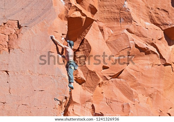 A climber ascends the red rock face of Elephant Butte in Sedona, Arizona.